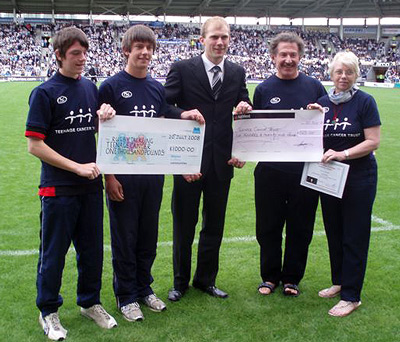 Cheques being presented at the derby match